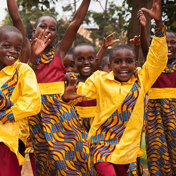 African Childrens Choir Dancing Together in yellow and red